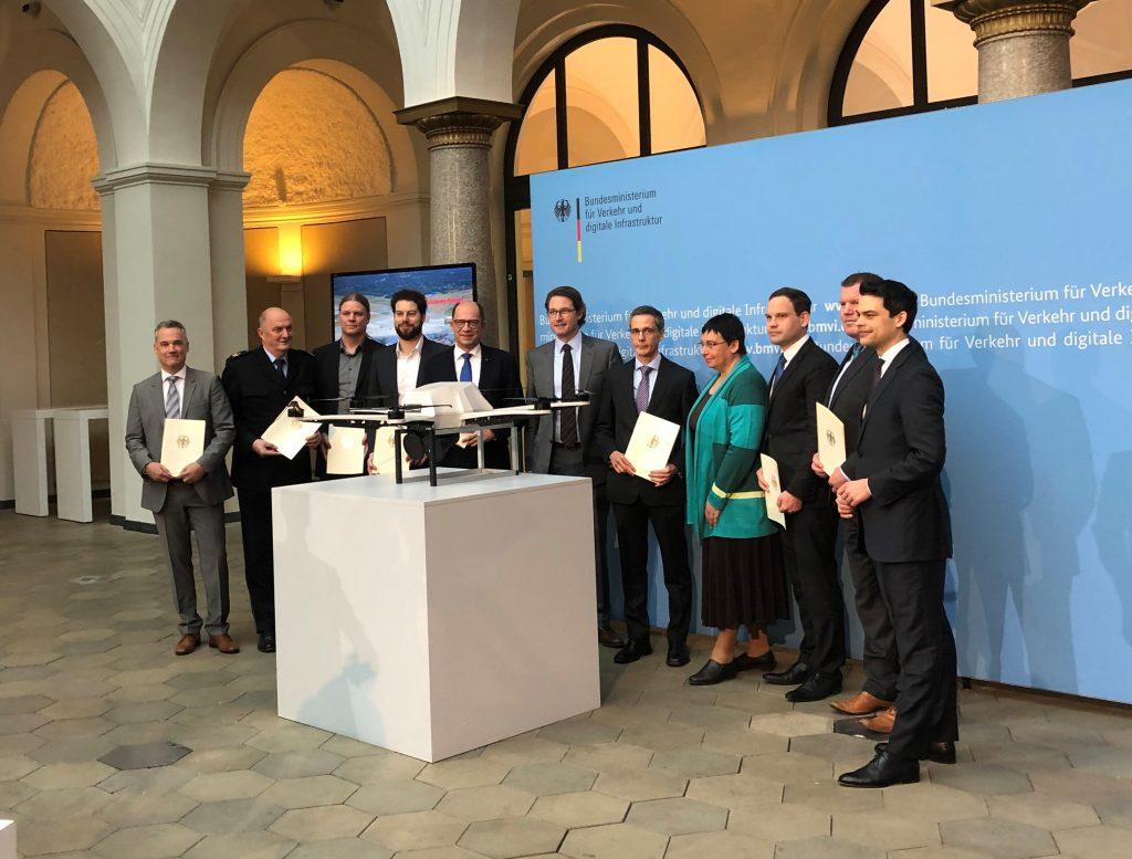 Eine Gruppe von Menschen, die Urkunden in den Händen halten. Der in der Mitte ist Bundesverkehrsminister Andi Scheuer.