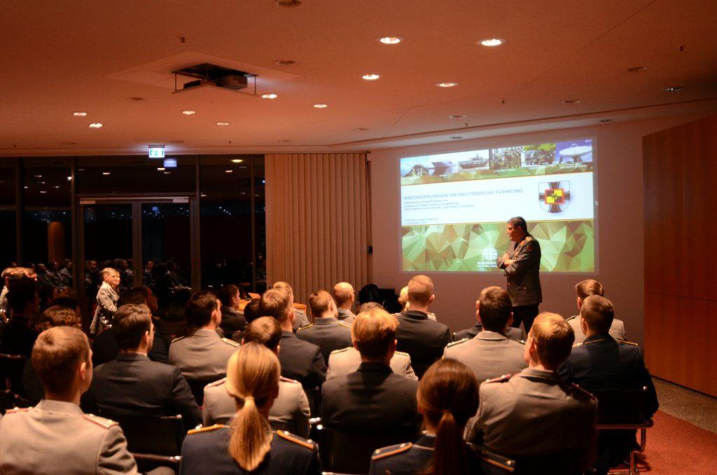 Ein Mann in grauer Uniform hält vor einem Publikum einen Vortrag