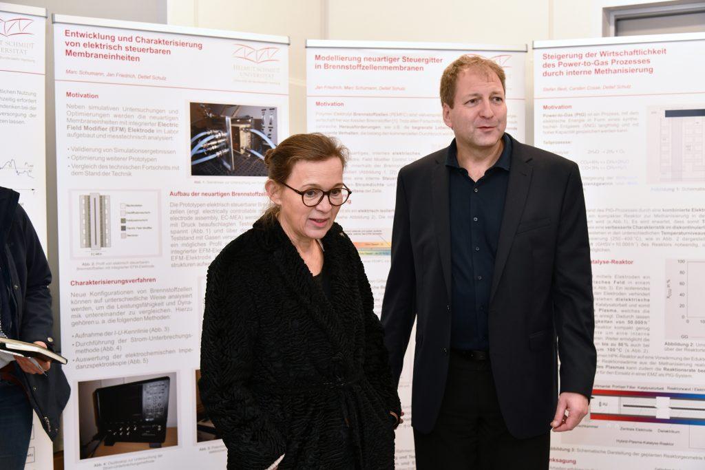 Eine Dame in einem schwarzen Mantel und ein Mann im dunklen Anzug vor einer Reihe von Postern