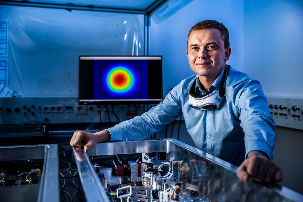Ein Mann steht hinter einem technischen Gerät. er trägt ein blaues Hemb