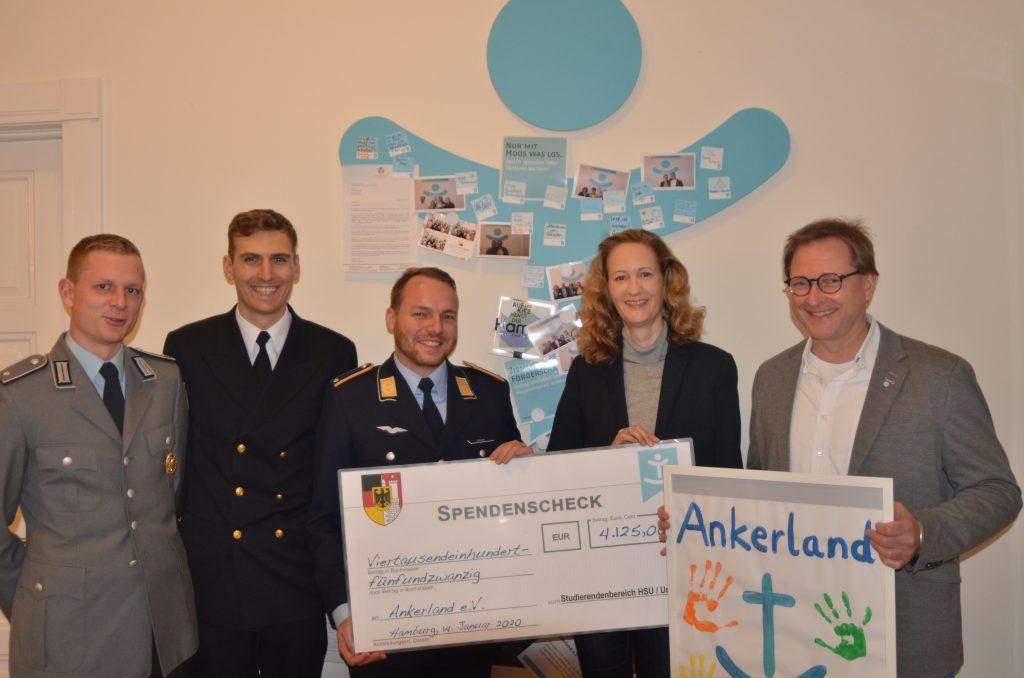 Drei Männer in Uniform übergeben einen Spendenscheck an eine Frau und einen Mann.