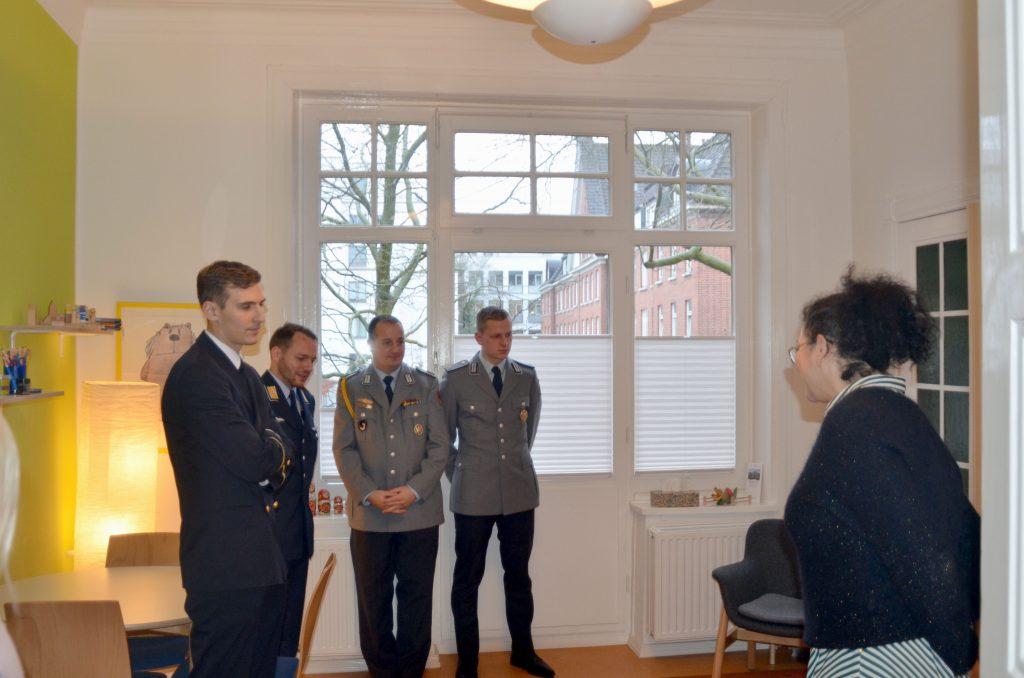 Eine Dame gibt vier Soldaten in Uniform eine Erläuterung.