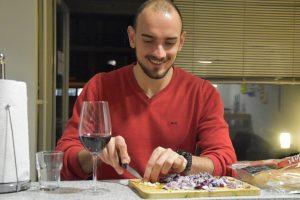 Ein junger Mann im roten Pulli schneidet Zwiebeln, im Vordergrund ein Rotweinglas
