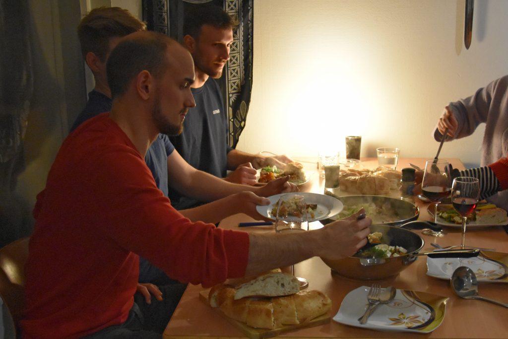 Drei junge Männer sitzen bei gedämpftem Licht an einem Tisch und essen.