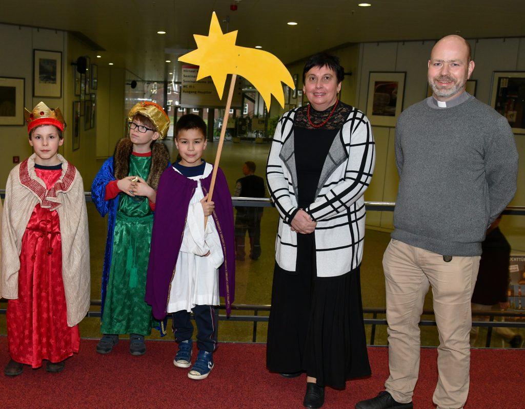 Drei Sternsingerkinder, eine Dame im schwarzen Kleid und ein Geistlicher mit Kollar.