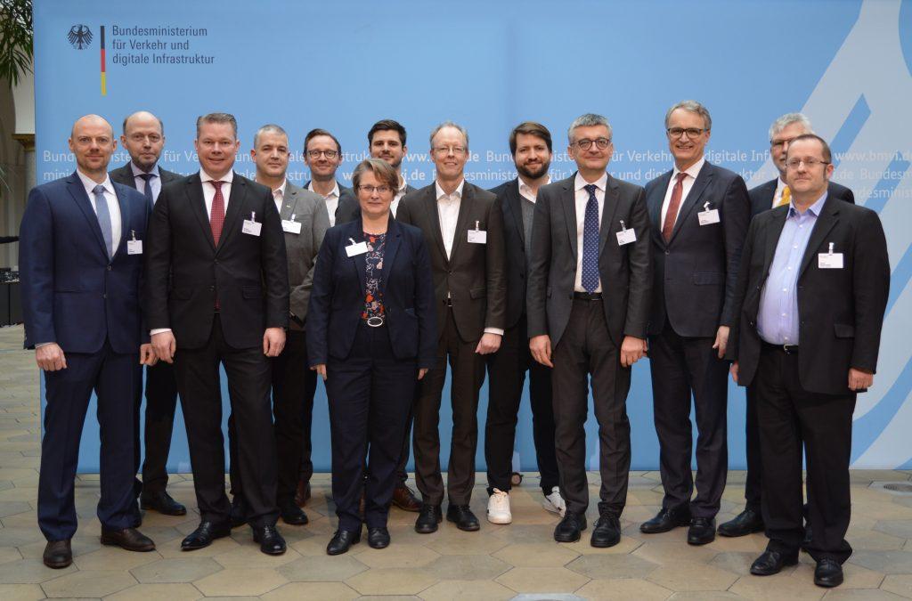 Eine größere Zahl von Männern und Frauen steht vor einer hellblauen Wand mit dem Logo des Bundesministeriums für Wirtschaft und digitale Infrastruktur