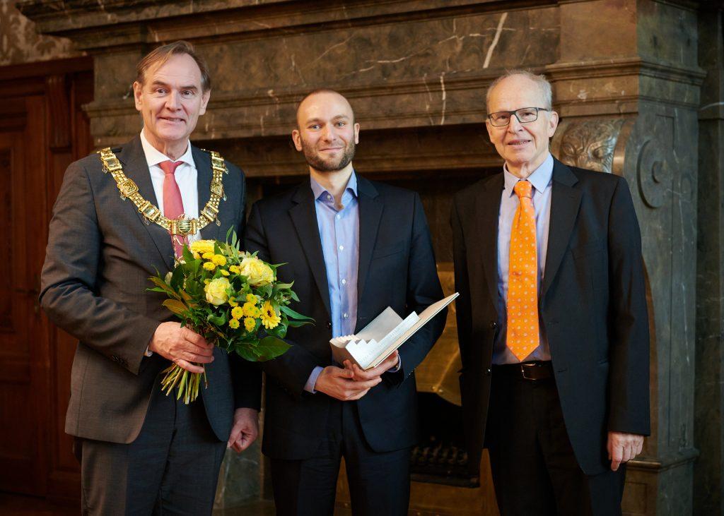 Drei Männer, der linke trägt eine Bürgermeisterkette, der mittlere eine Urkunde, der rechte eine leuchtend-orange Krawatte.