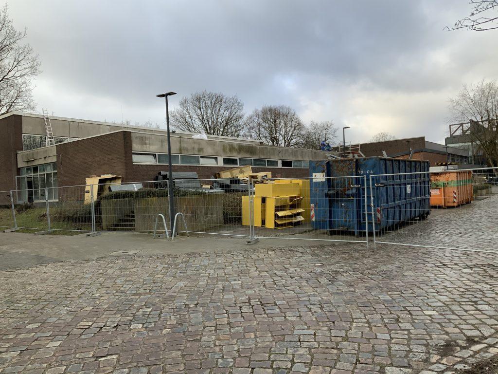 Container und Schrott stehen hinter einem bauzaun und vor einem Gebäude
