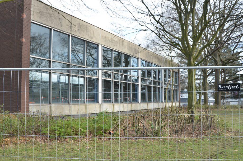 Ein Bauzaun, der die Glasfassade eine Schwimmhalle umgibt