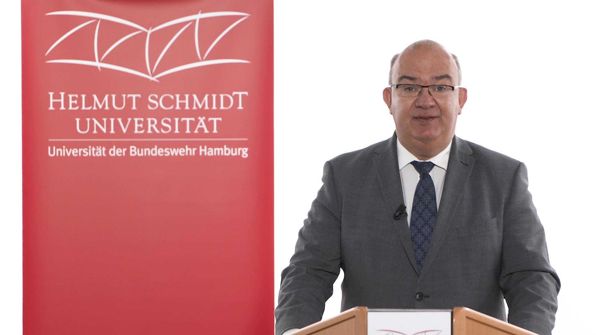 Ein Mann hinter einem Rednerpult, dahinter das Logo der Universität