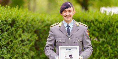 Ein Soldat in der Uniform eines Leutnants der Fernmeldetruppe des Heeres hält eine Urkunde in der Hand
