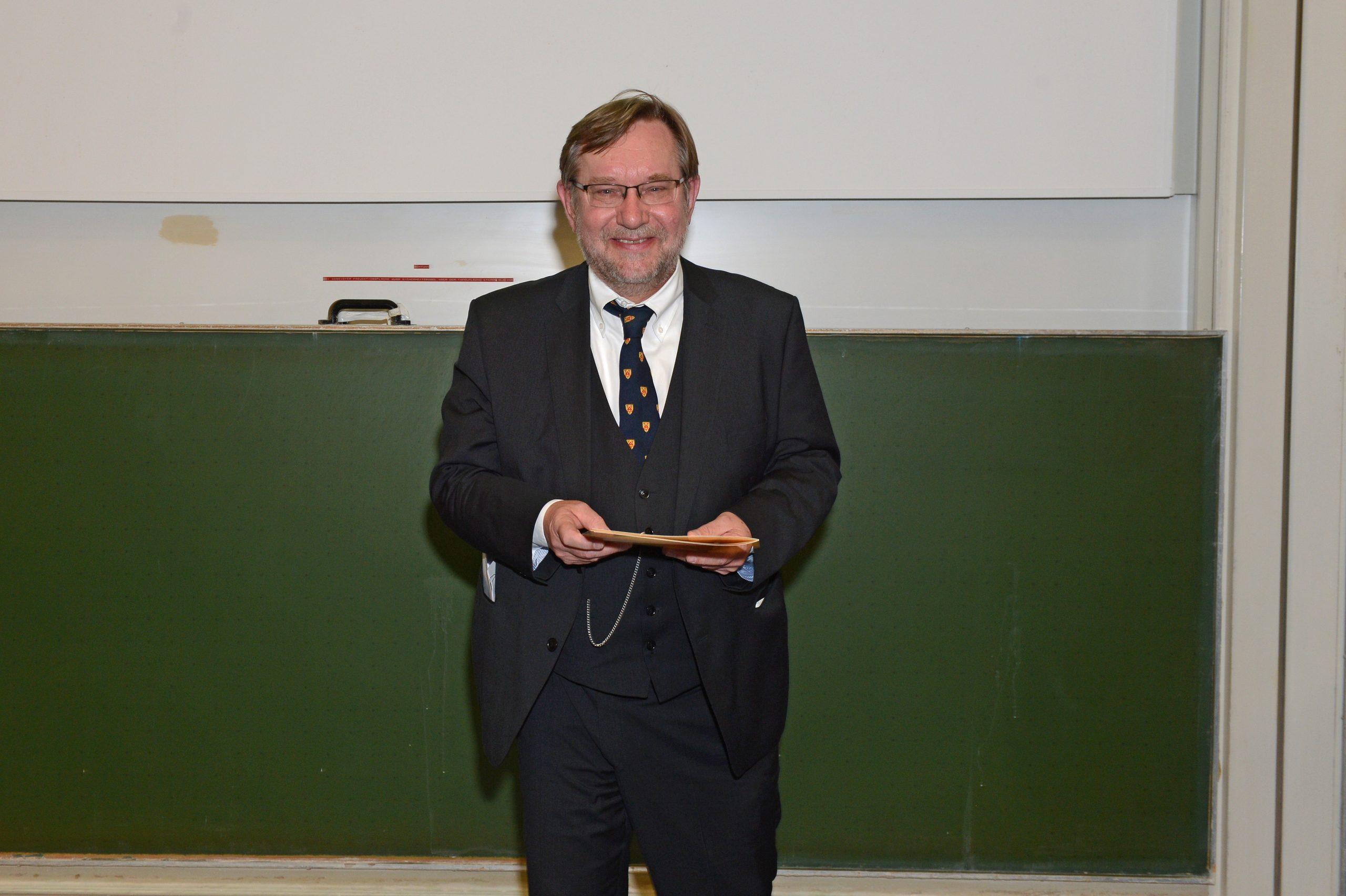 Ein Man in einem dreiteiligen Anzug mit gestreifter Krawatte vor einer Kreidetafel