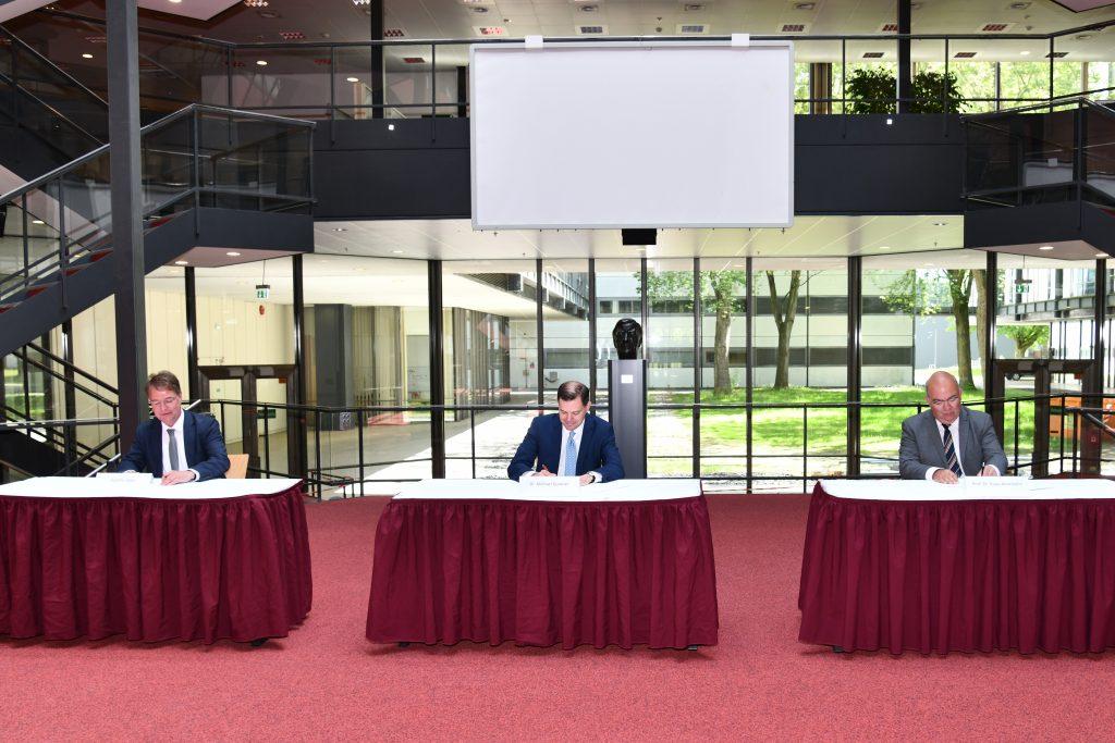 Drei Herren in Anzügen, die in einigem Abstand voneinander hinter drei Tischen auf einem roten Teppich sitzen, unterschreiben Urkunden.
