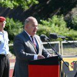 Ein Mann - es ist der Universitätspräsident - an einem Rednerpult, das mit der Bundesdienstflagge verkleidet ist. Dahinter steht ein Offizier.