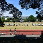 Panoramablick über eine größere Zahl von Soldaten, die auf einer Rasenfläche vor einem markanten gebäude (es ist die Mensa der HSU) angetreten stehen.