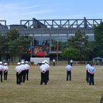 Angetretene Soldaten stehen vor einer 5 mal 3 Meter großen LED-Video-Wand, auf der eine Dame in einem roten Kostüm (es ist die Bundesministerin der Verteidigung) zu sehen ist