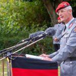 Ein Mann in der Uniform eines Oberst des Heeres hinter einem Rednerpult