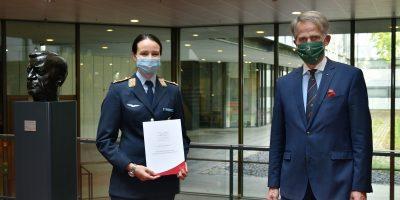 Eine junge Frau in einer Leutnantsuniform der Luftwaffe und ein eitwas älterrer Mann im blauen Anzug mit Krawatte neben der Büste von Helmut Schmidt; sie hält eine Urkunde in der Hand