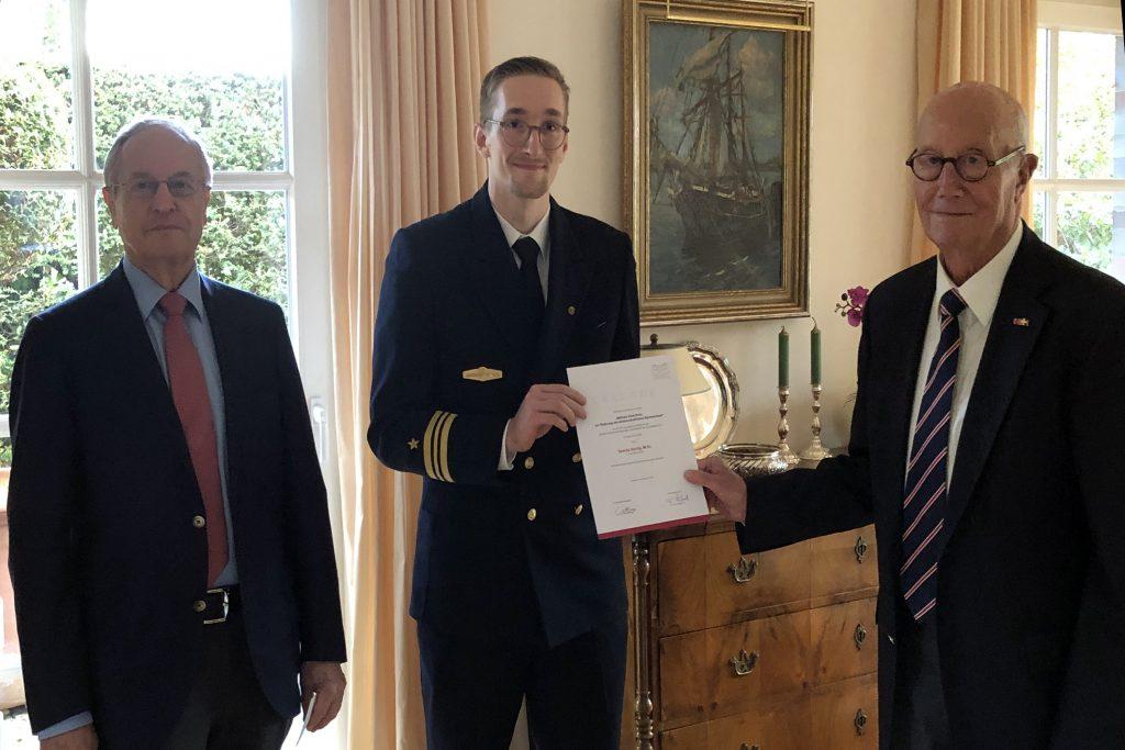 Zwei ältere Herrn im Anzug, in der Mitte in jüngerer Mann in der Uniform eines Kapitänleutnants der Marine, der eine Urkunde hält
