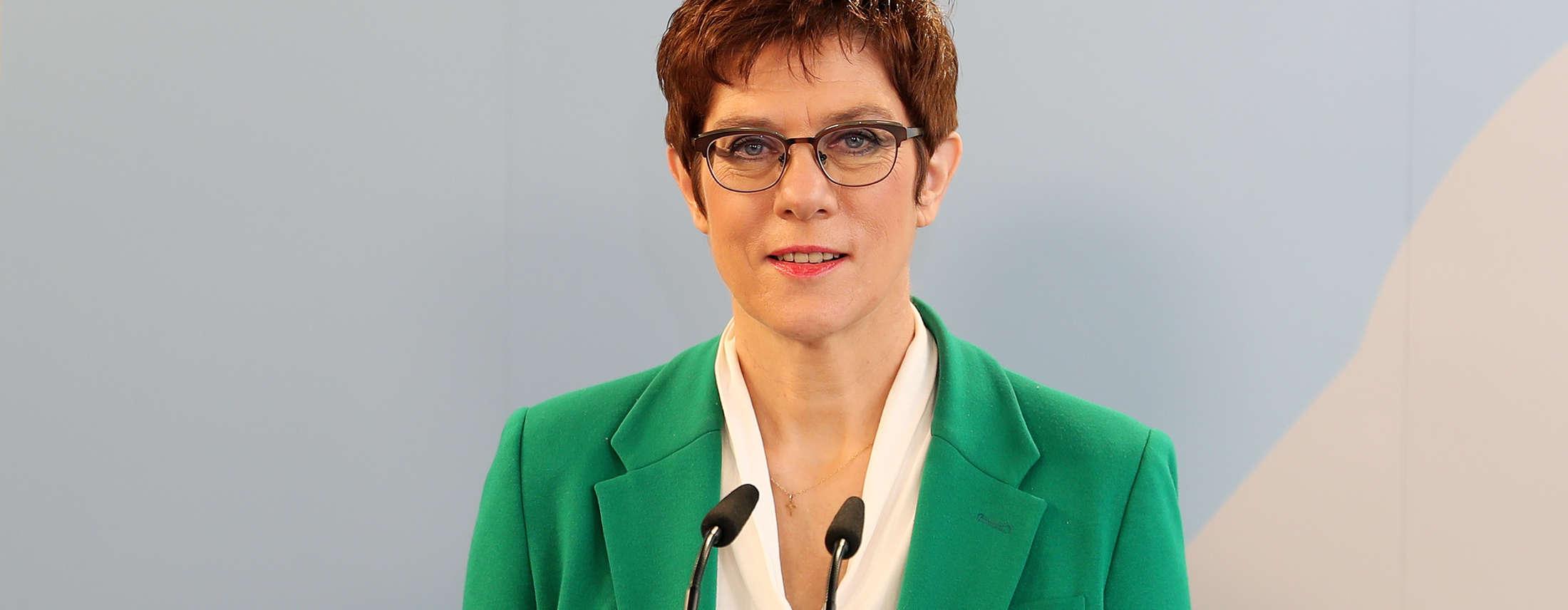 Eine Frau in einem grünen Blazer hinter einem Rednerpult