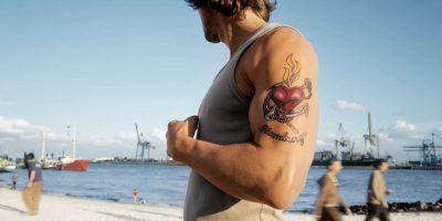 Ein Mann mit einem tätowierten Oberarm am Elbstrand