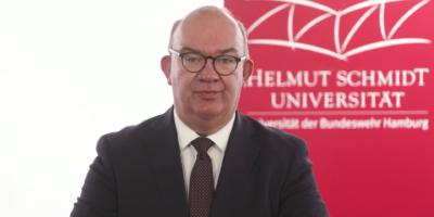 Ein Mann (er ist der Universitätspräsident) hinter einem Rednerpult, dahinter das Logo der Universität