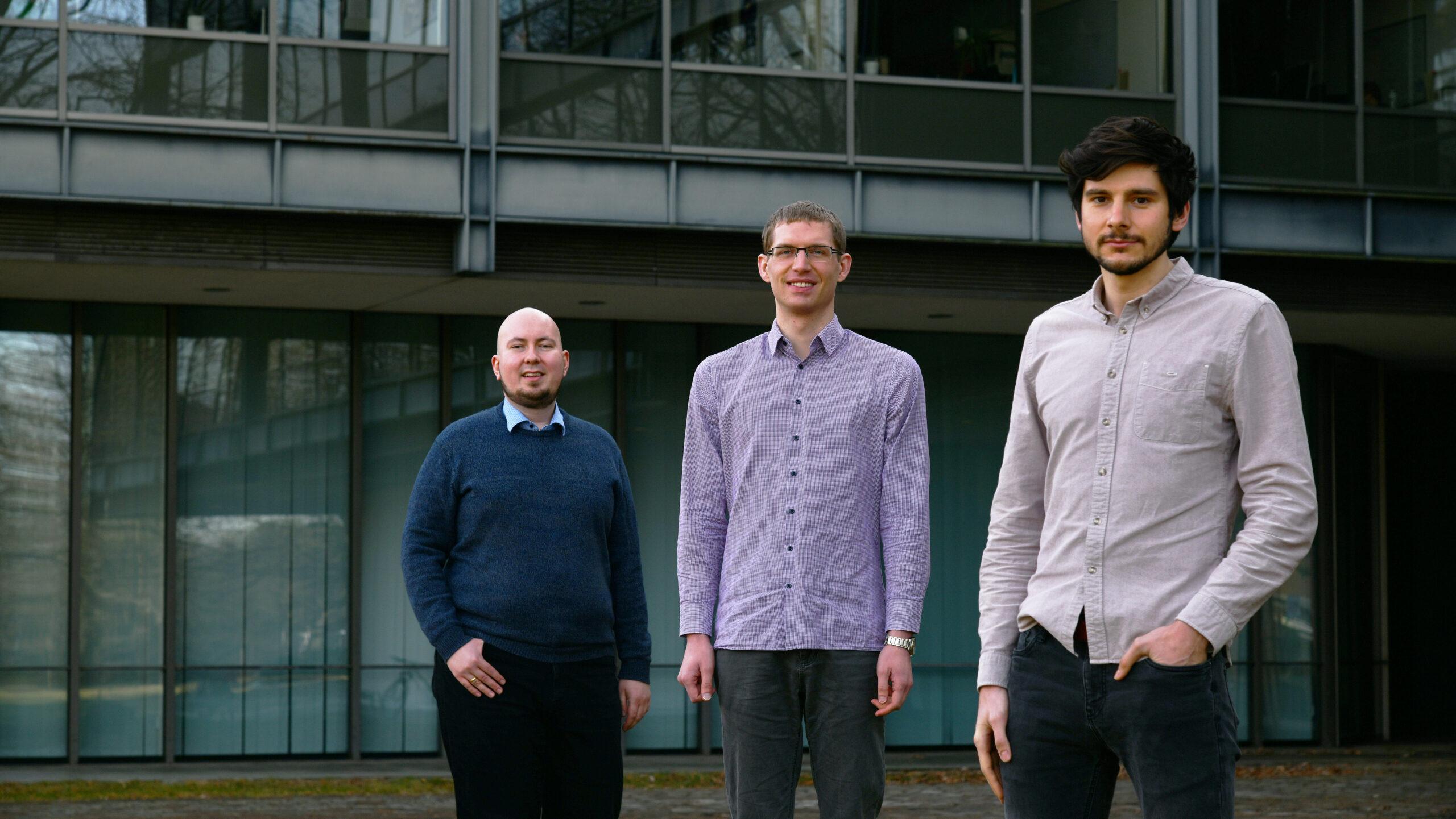 Drei junge Männer stehen vor dem Universitätsgebäude