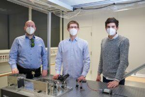 Drei junge Männer hinter einem Labortisch mit einem Laser