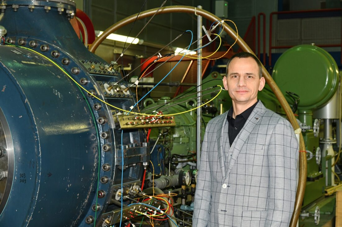 Ein Mann in einem grau-blau-karierten Anzug vor einer Turbine