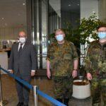 Drei Männer, einer im grauen Anzug, die anderen beiden im Feldanzug der Bundeswehr.