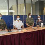 Vier Menschen mit Mund-Nasen-Bedeckung hinter Glasscheiben
