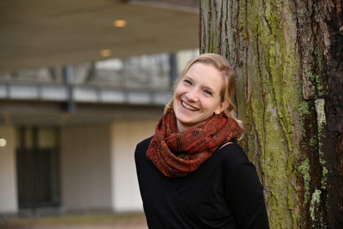 Eine blonde junge Frau, die an einem Baum lehnt. Im Hintergrund das Universitätsgebäude.
