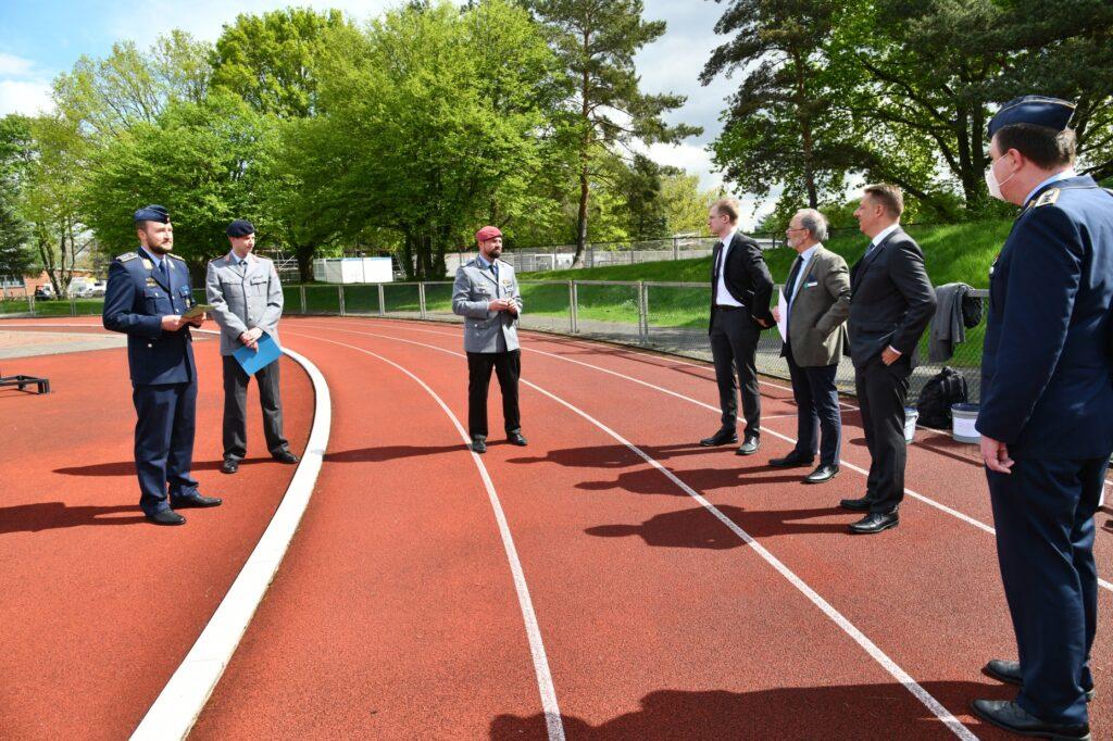 Drei Offiziere und vier Männer stehen sich auf einem Sportplatz gebenüber.