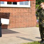Eine Frau, es ist die Verteidigungsministerin, hält eine Urkunde in der Hand. Ein Soldat salutiert.