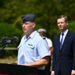 Ein Mann in der Uniform eines Oberst der Luftwaffe spricht in zwei Mikrofone.