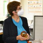 Eine Ftrau mit Mund-Nasen-Schutz (es ist die Bundesministerin der Verteidigung) mit einem Bauteil in den Händen.