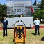 Zwei Männer, einer im blauen Anzug, der andere in der Uniform eines Luftwaffenpffiziers, stehen mit großem Abstand vor einer LED-Wand. Im Vordergrund ein Rednerpult, das mit der Bundesdienstflagge verkleidet ist.