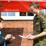 Eine Frau (sie ist die Bundesministerin der Verteidigung) überreicht einem Soldaten einen Orden.