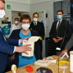 Mehrere Menschen mit Mund-Nasen-Schutz. Links zeigt ein Mann einer Frau einen Behälter. Die Ftrau ist die Verteidigungsministerin.