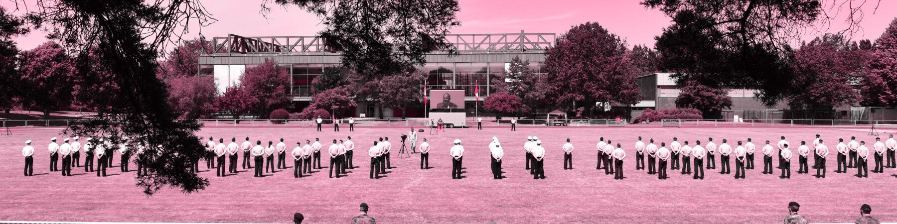 In Rot, der Farbe der Universität, eingefärbtes Panoramabild von angetretenen Soldaten auf einem Sportplatz