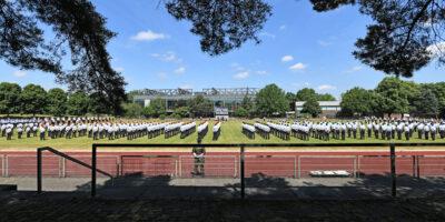 Soldaten stehen mit großem Abstand auf einem Rasenplatz angetreten.