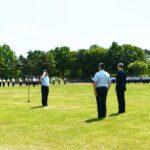 Ein Luftwaffenoffizier salutiert vor einem anderen Luftwaffenoffizier und einem Mann im blauen Anzug