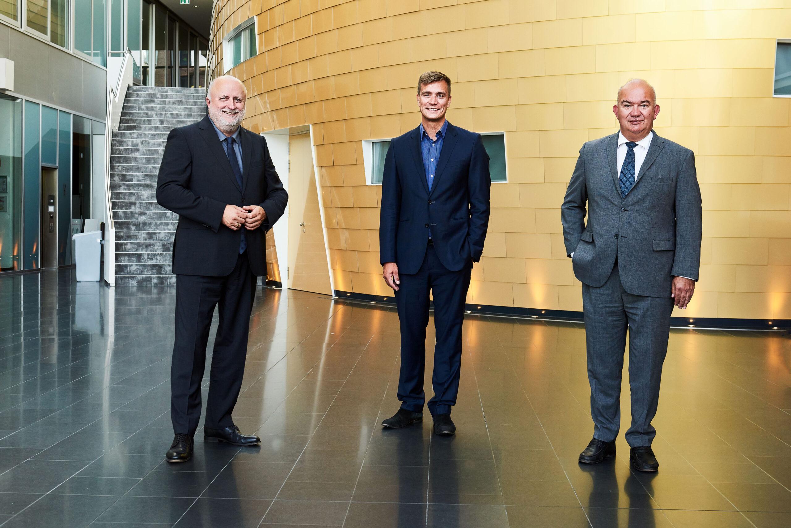 Drei Herren in Anzügen stehen vor einer futuristisch anmutenden Wand