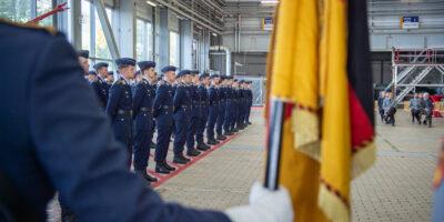 Soldaten in Luftwaffenuniform, davor eine Faust mit weißem Handsschuh, die die Bundesdienstflagge hält.