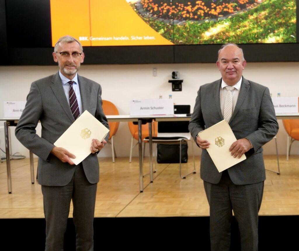 Armin Schuster, Präsident des Bundesamtes für Bevölkerungsschutz, und Prof. Dr. Klaus Beckmann, Präsident der Helmut-Schmidt-Universität / Universität der Bundeswehr, unterzeichnen die neue Lehrkooperation.